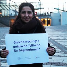 """Eine Frau hält ein Schild auf dem steht """"Gleichberechtigte politische Teilhabe für Migrantinnen."""""""